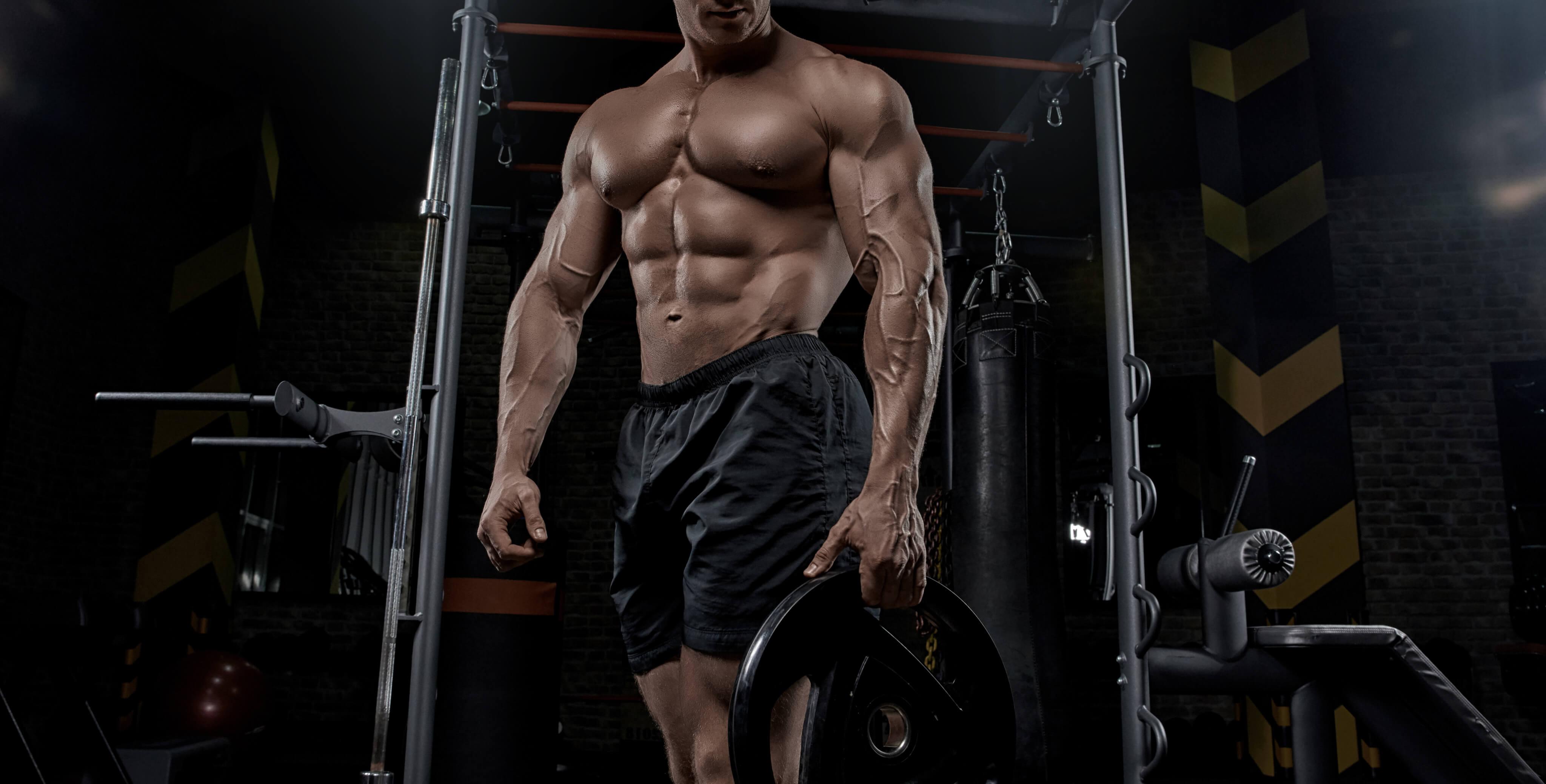 Muskulös man styrketränar på gymmet.